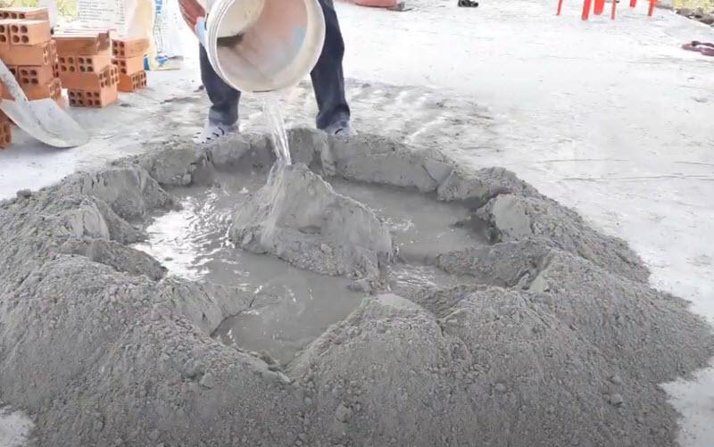 Đổ nước vào xi măng và cát đá trộn khô trước đó